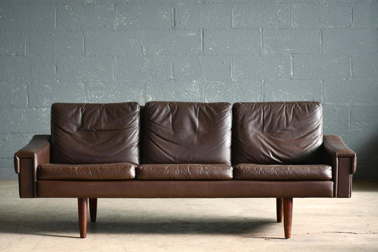 Classic Danish midcentury three-seat leather sofa in a nice warm chestnut color designed by Georg Thams in the 1960s and manufactured by Vejen Polstermobelfabrik in Denmark. Very elegant yes relaxed with leather inserts on the front of the armrests