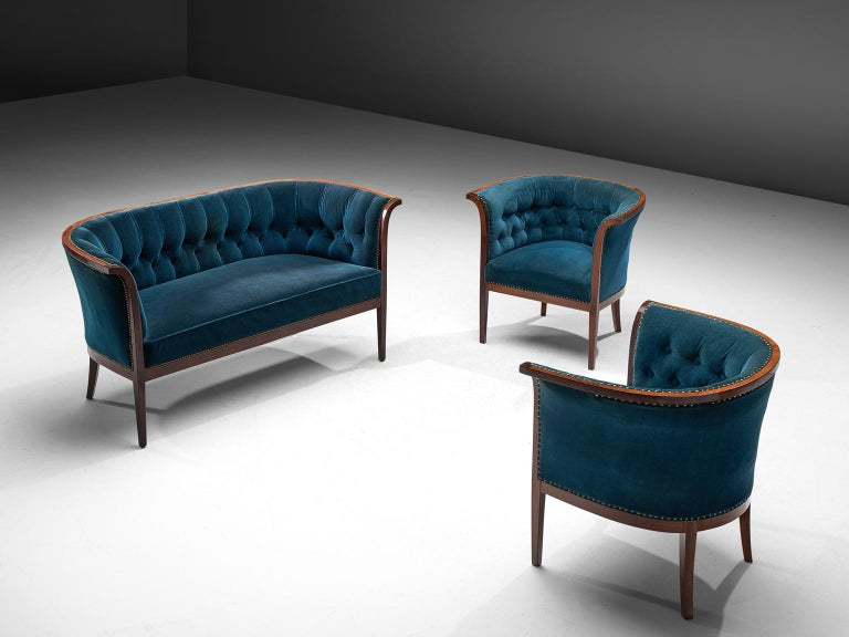 Three-seat sofa and two armchairs, blue velvet upholstery, wood, Denmark, 1940s.  This velvet blue Danish sofa and matching armchairs feature a backrest that is tufted and the seat is executed in one piece. The seat is thick and comfortable. The