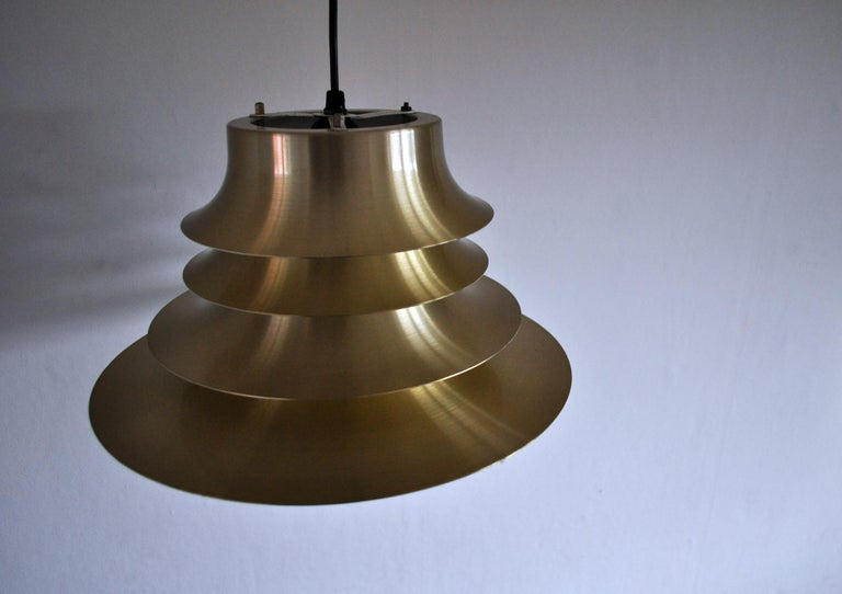 A classic Danish multilayered pendant light in brass with a white enameled inner surface. Measures: Diameter 35 cm, height 18 cm. Fine vintage condition.