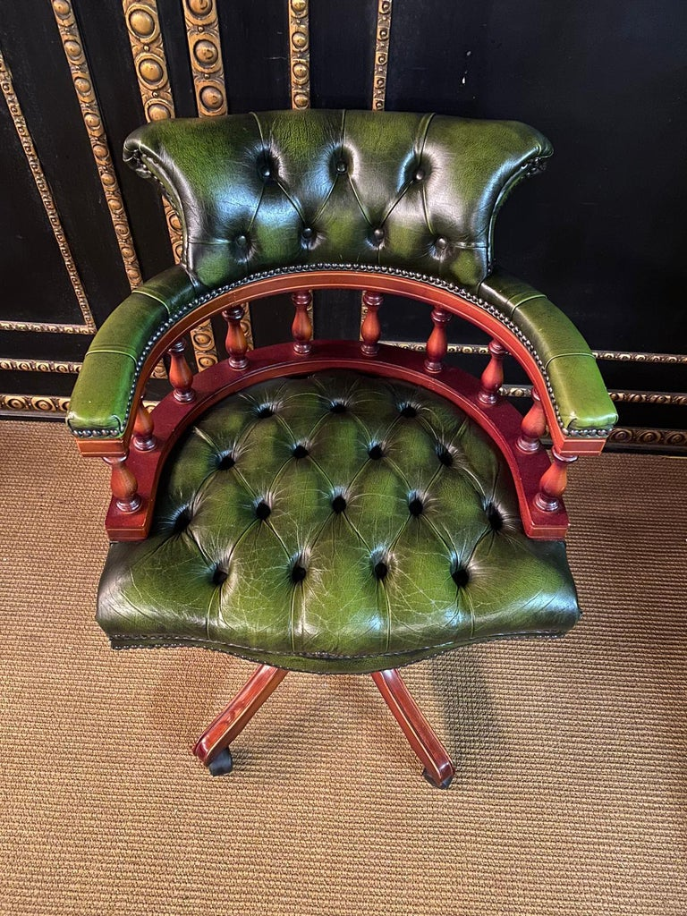 Chesterfield office swivel chair on castors. Fully quilted leather. At the front of the armrests, the leather is slightly damaged Beautiful green, with over decades grown dreamlike patina. With its own charm, this shapely armchair enchants every