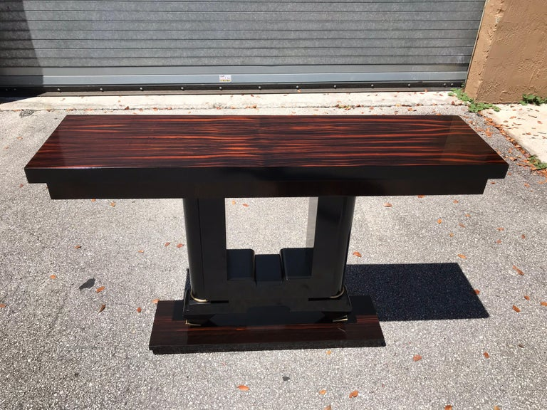 French Art Deco exotic Macassar console table, circa 1940s. Beautiful Macassar ebony with black lacquer base, finish in both side, with beautiful bronze hardware detail, that rest on makes it ideal for use as a bedside table or for the foyer room or