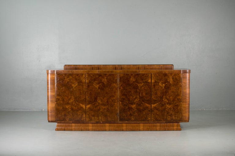 French Art Deco Classic burr walnut sideboard or buffet, circa 1930s. This luxurious piece was originally made in Strasbourg (France) in the 1930s. The sideboard features five inside drawers, a marble tablet and two shelves. The curved lines of this