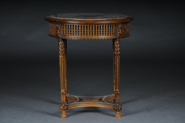 Classic French side table in Louis XVI, beechwood  Hand carved solid beechwood. Round relieved frame base on fluted legs. Below connected center bar. Round, low-profile, framed tabletop with marble slab embedded in it. (G - 78).