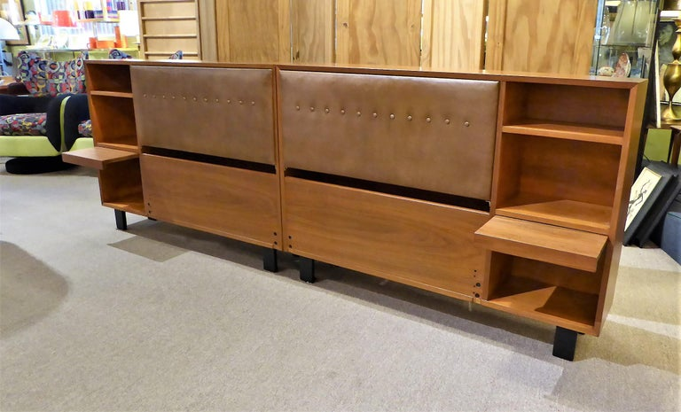 Smart and classic George Nelson design for the Herman Miller collection of the early 1950s, this pair of walnut King headboard storage units with bedside shelves and pull out tables are quite beautiful and utile. Consisting of a mirror image left