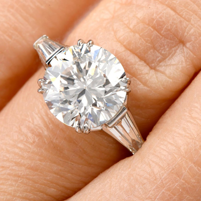 This classic diamond engagement ring is hand-crafted in solid platinum.  Center exposes a high quality Round Brilliant-Cut, GIA Certified, Weighing approx. 4.12 carats. Graded F Color,  SI1 Clarity, 4 prong-set. Diamond Measuring 10.20mm-10.38mm x
