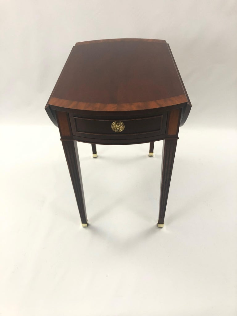 A Classic mahogany pembroke style drop leaf side table by Baker, having lovely banded inlay, single drawer, elegant tapered legs, and when open becomes an oval.