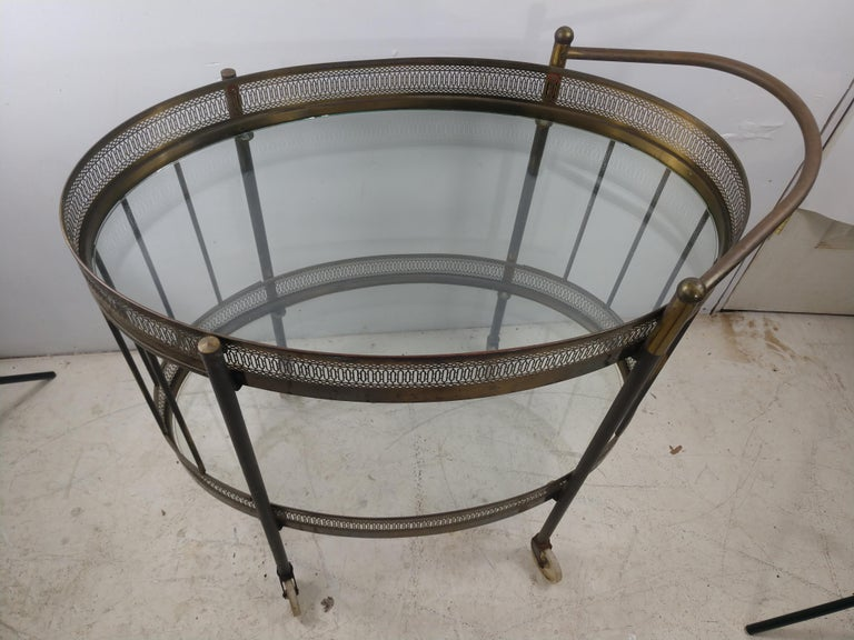 Solid brass bar cart with reticulated aprons. Brass is unpolished and in very good condition. Two tiers of glass shelving.