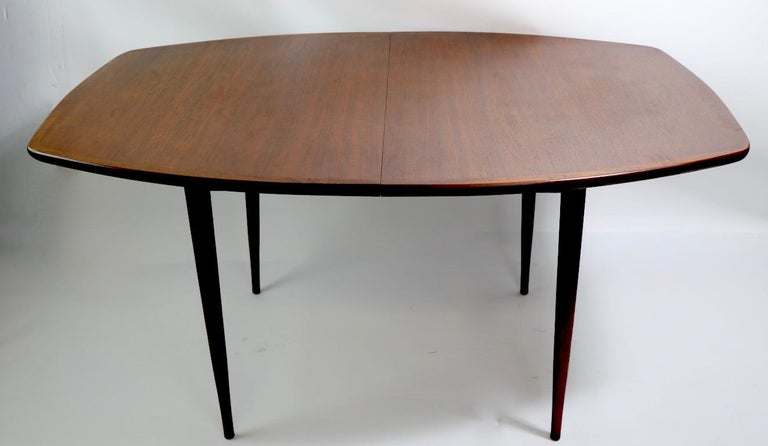 Classic mid century dining table, well crafted of solid wood, with elegant architectural lines, clean, original, ready to use condition. The table has two original leaves each 18. W with both leaves in place 94 inch x W without leavers 58 inches.