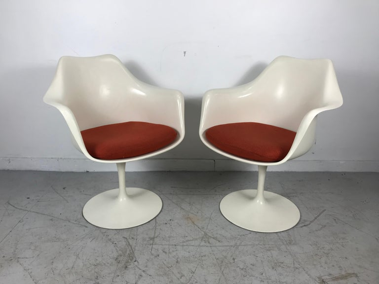 Mid-Century Modern dining chairs designed by Eero Saarinen. Chairs feature the original upholstered seats (minor blemishes) on a white enameled cast iron pedestal base.Also retain original early Knoll labels,, Manufactured by Knoll & Associates in