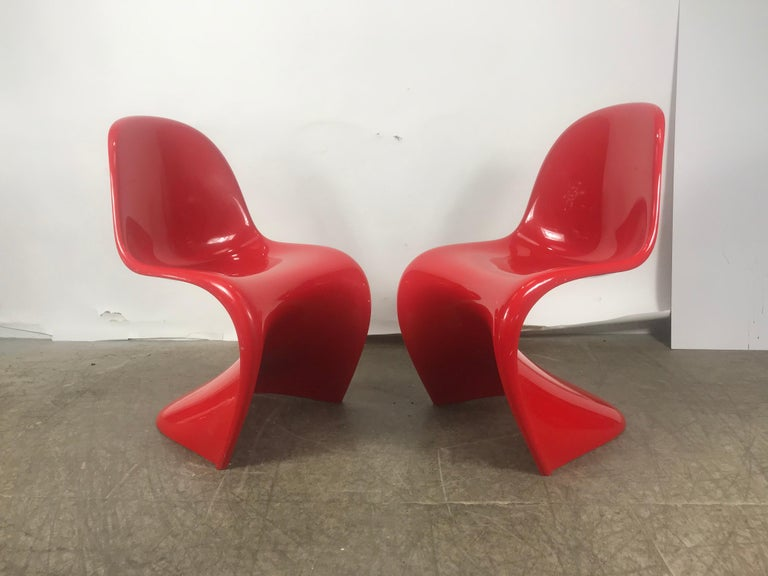 An iconic red stacking chair by influential Danish architect and designer Verner Panton (1926-1998). Designed in 1958, this cantilevered, stackable chair is the first single-form, injection-molded plastic chair ever produced. A masterpiece of design