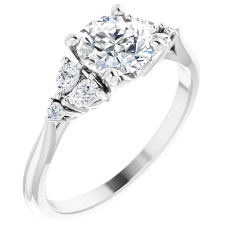 Pear shape and round diamonds shine with brilliance as they line the shank of this classic style engagement ring. Handcrafted in 18k white gold, the matching wedding band complements this bridal wedding set.    Style Number: