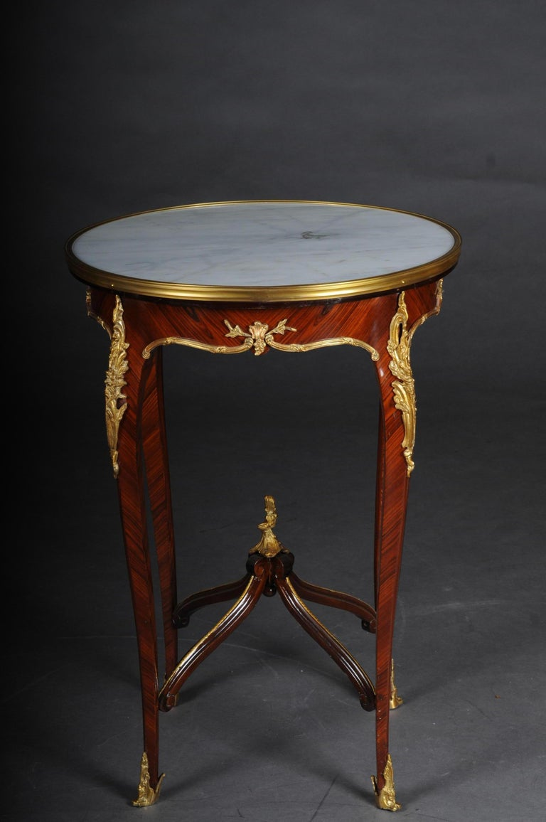Classic saloon side table in the Louis XV after F. Linke.  Veneer on solid beech, daintily finished, body, flanked by solid corner strips on high, elegantly curved legs with bronze fittings ending in sabots. Slightly protruding, round marble top