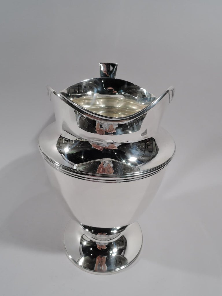 Classic sterling silver water pitcher. Made by Tiffany & Co. in New York, circa 1911. Curved and tapering body, raised and stepped foot, scrolled bracket handle, and helmet mouth. Reeding. Fully marked including pattern no. 18181 (first produced in