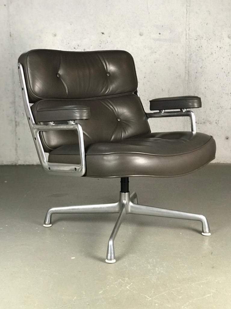 Executive lounge chair by Charles and Ray Eames. Original condition. Original grey leather with a light brown hue. The aluminum frame has wear/abrasions - leather has some wear as well. Indintation in the top. Faint crease along the top of the back