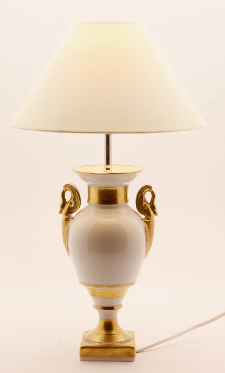 Porcelain table lamp base with ivory pastel glaze and gilded details (handles neck, foot and pedestal) on a white body. Following the classical outline and using the experience of 130 years making porcelain.  Marked on the base: Porcelaine De
