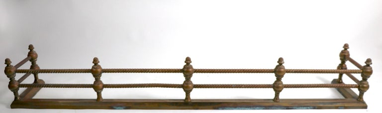 Brass fender, with twisted rail horizontal rods held by classical styled vertical supports. Total H 10 inch, top rail H 8 inches. Finish shows patina and wear, normal and consistent with age. Solid brass construction.