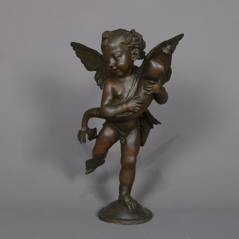 A Classical and figural bronzed metal sculpture fountain head features young Neptune as winged cherub with fish, 20th century  Measures: 29