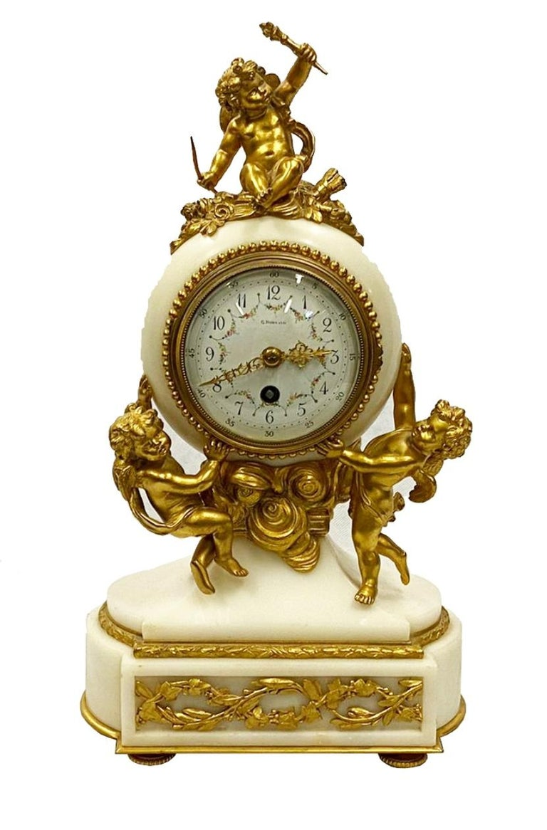 An enchanting 19th century Louis XVI style clock garniture, having gilded ormolu mounts with three cherubs with ribbon swags, the white enamel clock face with an eight day chiming movement and raised on a plinth base. Either side are matching