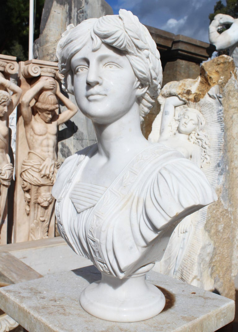 Classical hand carved white marble bust of a woman wearing Greek period dress and a laurel wreath.