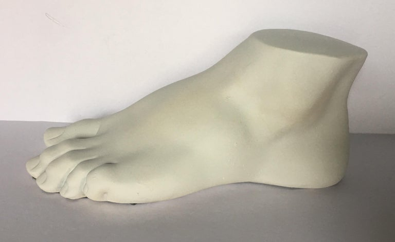 Neoclassical style plaster cast foot fragment sculpture featuring a warm cream matte finish. An interesting tabletop accessory for any Hollywood Regency interior.