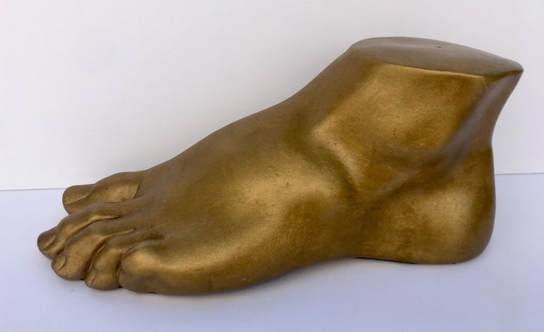 Neoclassical style plaster cast foot fragment sculpture featuring a patinated gold metallic finish. An interesting tabletop accessory for any Hollywood Regency interior.