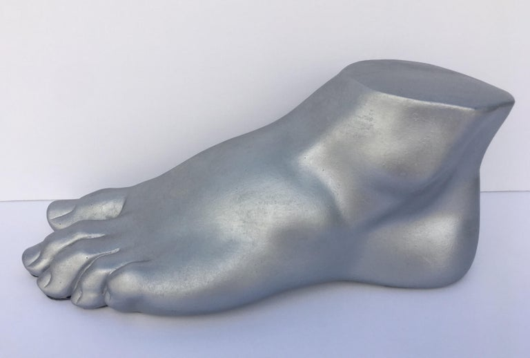 Neoclassical style plaster cast foot fragment sculpture featuring a patinated silver metallic finish. An interesting tabletop accessory for any Hollywood Regency interior.