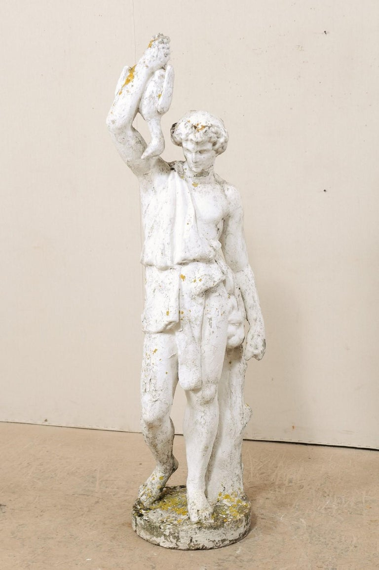 A tall French garden sculpture of male figure from the early 20th century. This antique cast-stone statue from France features a male figure, draped in classical attire, standing against a small tree trunk, with hand raised to display a hanging