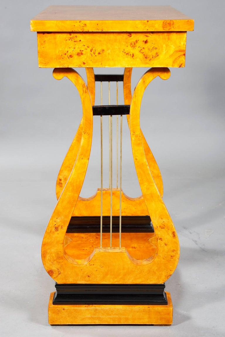 Maple root on solid softwood. Straight, on lyre-shaped, openwork cheeks with metal sides. Seal-shaped base plate. Upper drawer with compartments. protruding rectangular plate. Beautiful patina, with shellac hand polish. Literature reference: Georg