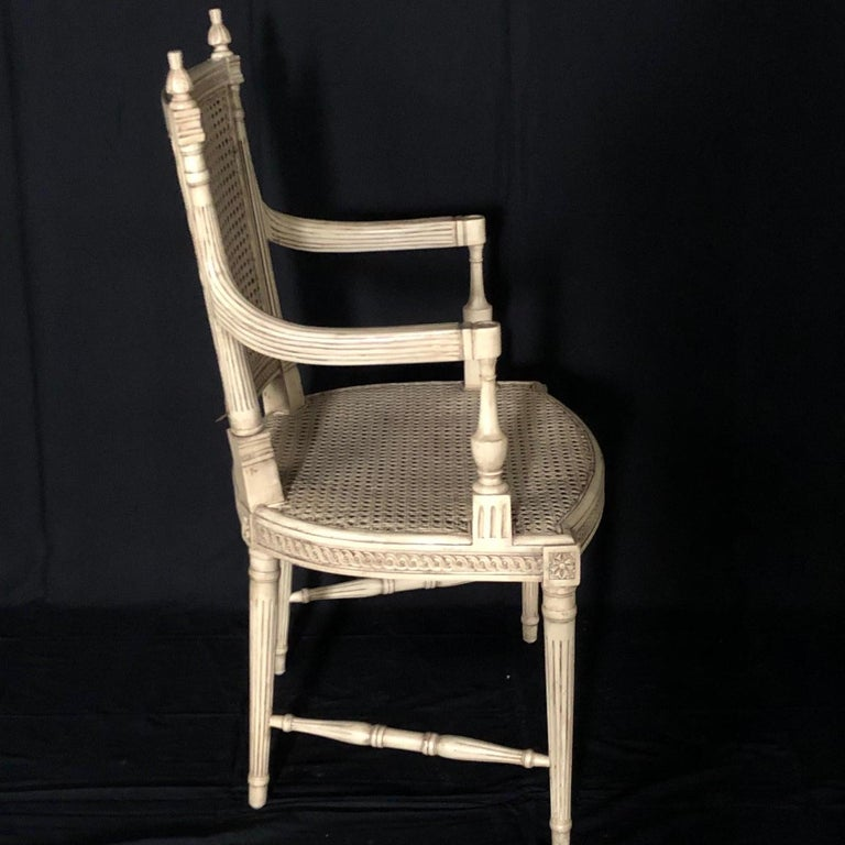 Beautiful ivory painted Louis XVI style armchair having double caning, in great condition! Reeded legs and intricate scrolling on apron and top of backrests are complemented with carved finials.  #5109.