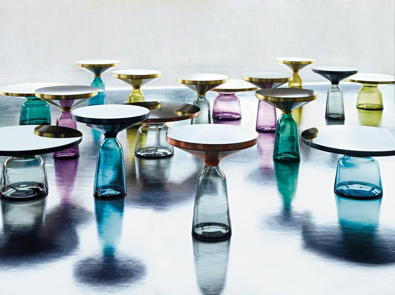 The bell table by Sebastian Herkner turns our perceptual habits on their head, using the lightweight, fragile material of glass as base for a metal top that seems to float above it. Hand blown in the traditional manner using a wooden mold, the