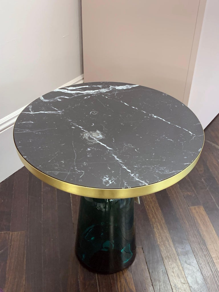 Nero Marquina marble top The bell table by Sebastian Herkner turns our perceptual habits on their head, using the lightweight, fragile material of glass as base for a metal top that seems to float above it. Hand blown in the traditional manner