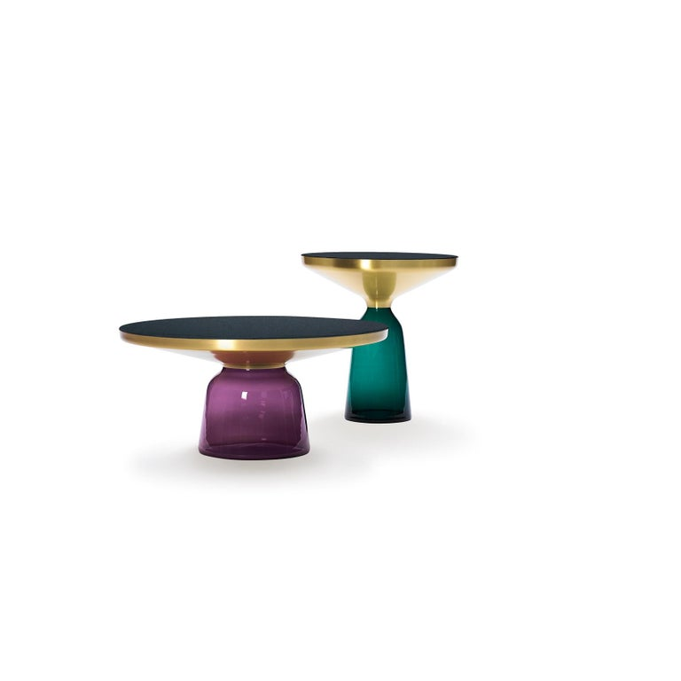 """The """"Bell Table"""" by Sebastian Herkner turns our perceptual habits on their head, using the lightweight, fragile material of glass as base for a metal top that seems to float above it. Hand blown in the traditional manner using a wooden mold, the"""