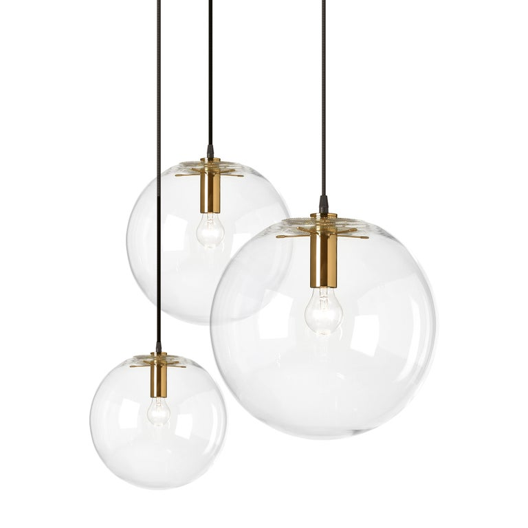 Handblown clear crystal glass sphere. Centrally suspended by a five-armed light head. Insect protection cover and light head in metal, brass-plated. Black fabric covered wire.