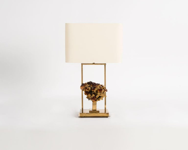 Claude Boeltz's table lamp sets clean, mechanically sculpted lines of brass against the asymmetrical, numinous beauty of naturally occurring objects. This piece's function is almost superseded by its form, for the lamp doubles as an illuminated