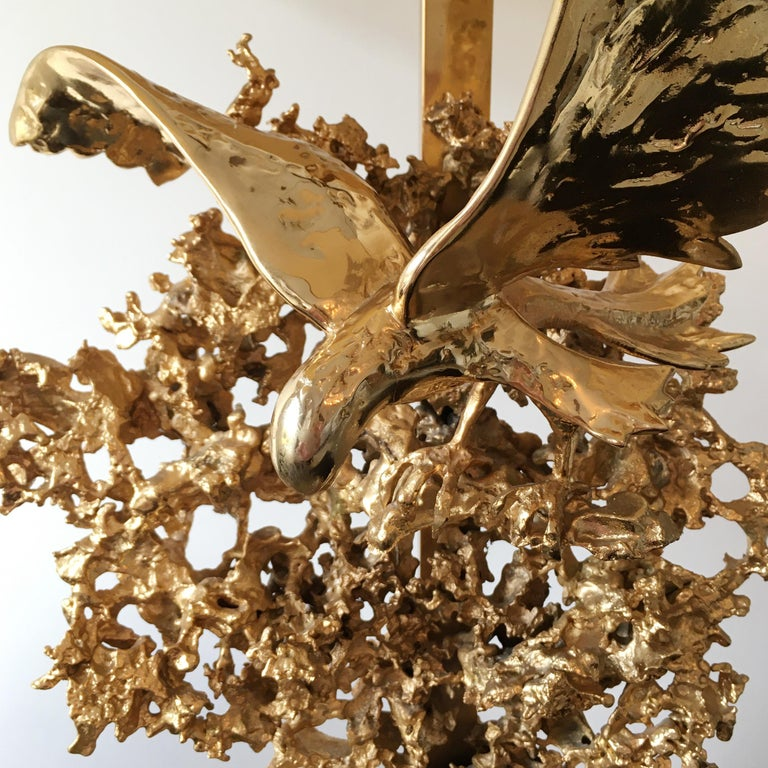 Claude Victor Boeltz sculptural 24-karat gold plated 'exploded' table lamp with eagle and rock crystal inclusions An incredible statement piece The natural rock quartz crystal wands are set into the base France circa 1970 The lamp has 3 bulb
