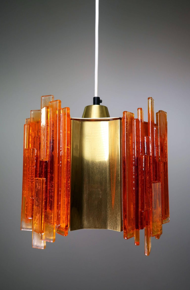 Danish Mid Century Scandinavian Modern Space Age octagon shaped pendant with four concave brass pieces intermixed with four orange acrylic pieces composed of many rectangular acrylic sticks arranged on top of each other to create a unique geometric
