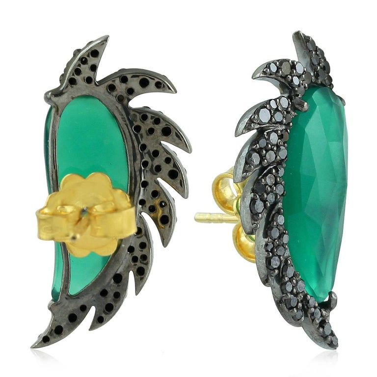 These distinctive stud earrings are modern twist to fine jewelry, handcrafted in 14K gold, sterling silver, green chalcedony and black diamonds. The iridescent 16.0-ct rose cut green chalcedony is surrounded by 0.67-ct signature diamond pave arches.