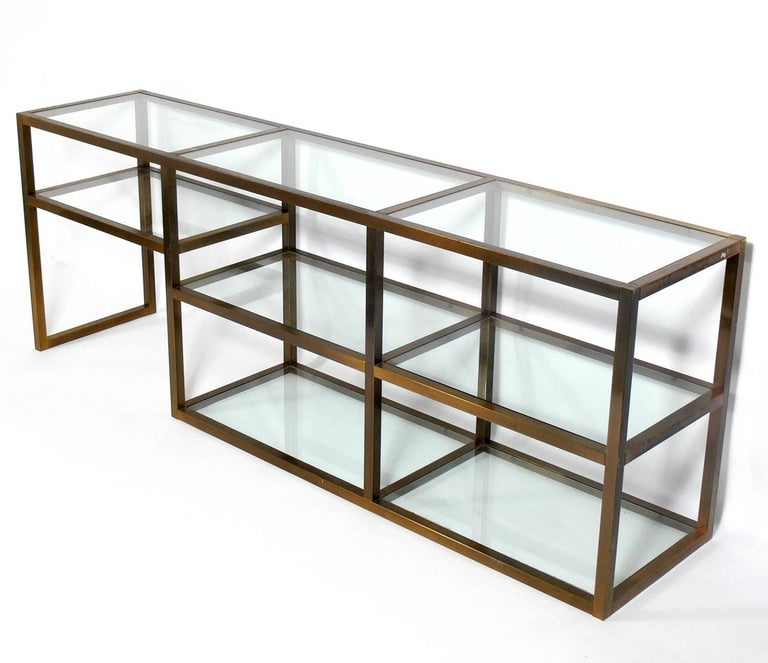 Clean lined brass and glass bookshelf or vitrine, American, circa 1960s. This piece is a versatile size and can be used as a bookshelf, vitrine, display case, bar, or media cabinet. Retains warm original patina to brass and brass plated metal.
