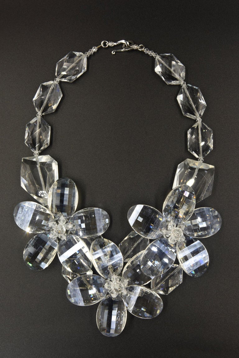 Impressive facetted lucite necklace featuring three large 5 - petal flowers in the center strung on large faceted clear lucite beads.  The back has a hook and eye closure.