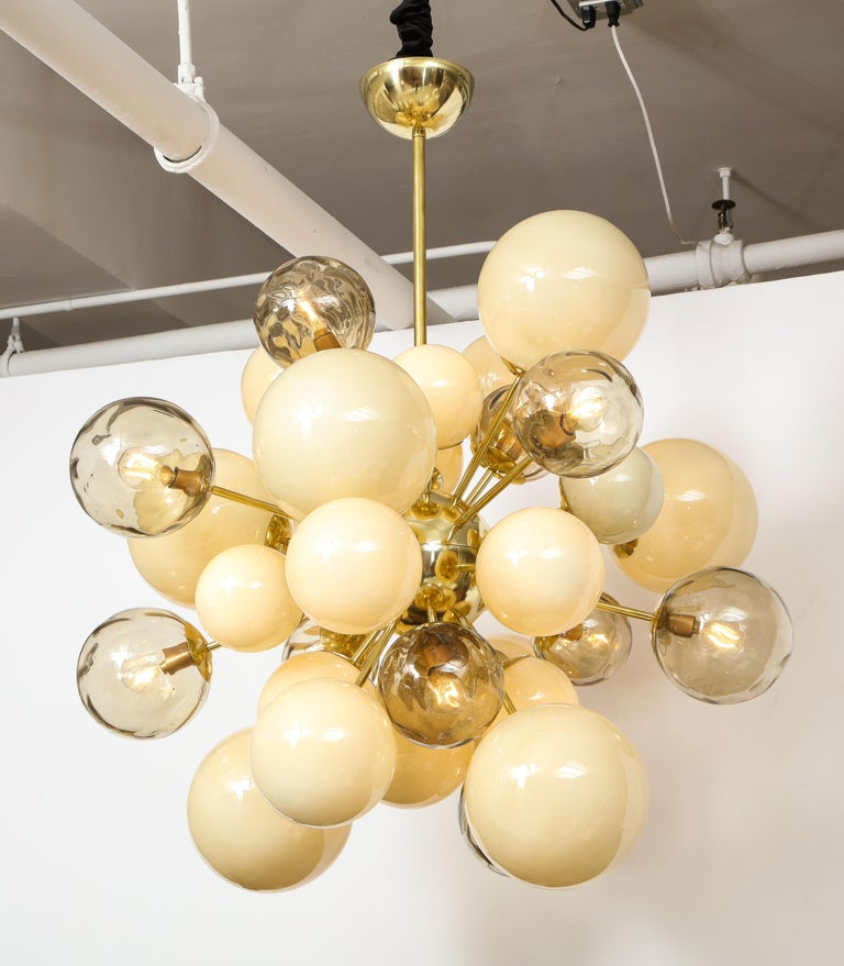 Unique Sputnik or starburst chandelier consisting of hand blown, ivory and smoked taupe Murano glass globes or spheres of various sizes in both clear and opaque glass finish. Each glass globe is connected to a brass rod which radiates from a brass