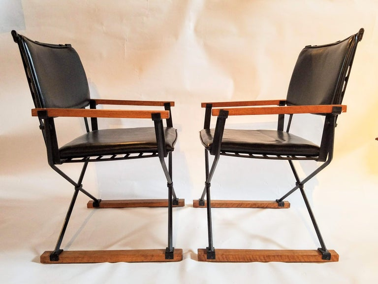 Cleo Baldon unusual pair of Campaign chairs manufactured by Terra in the mid-1960s thru the mid-1970s. The wrought iron chairs are lacquered in their original black color with fumed oak strips and clip on back cushions. This pair of chairs closely