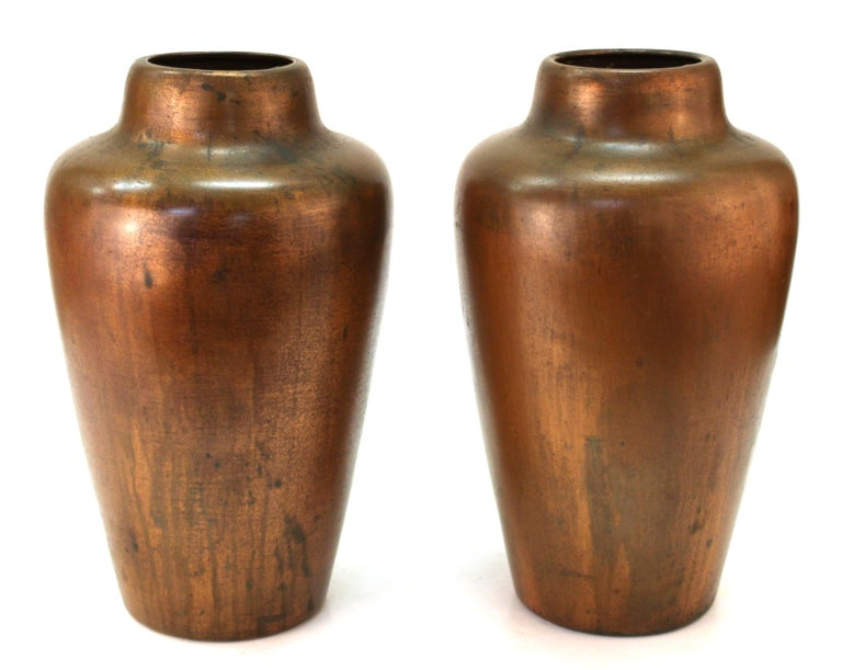 American Arts & Crafts movement pair of vases in copper-clad ceramic, created by American metal-smith Charles Walter Clewell (1876-1965) in the United States in the 1900s. Clewell was known for developing a secret technique for completely covering