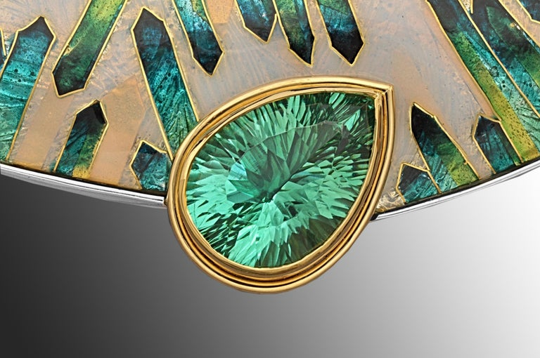 The asymmetric cloisonné enamel brooch is a one of a kind brooch and is named VERDANT. It is inlaid with 24 karat yellow gold. The enamel is bezel set in sterling silver and the 13.6 carat Appetite stone set in 18 karat yellow gold. This statement