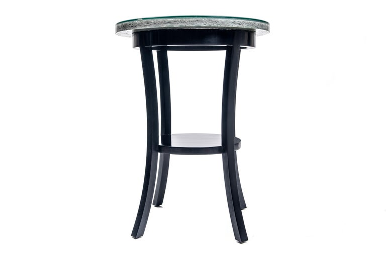 Made with alder, a glossy black finish, and polished crushed gloss, the clover table features flared legs and repeated circles to create visual interest in this elegant yet subtle design. Makes a statement in any formal living space or as a