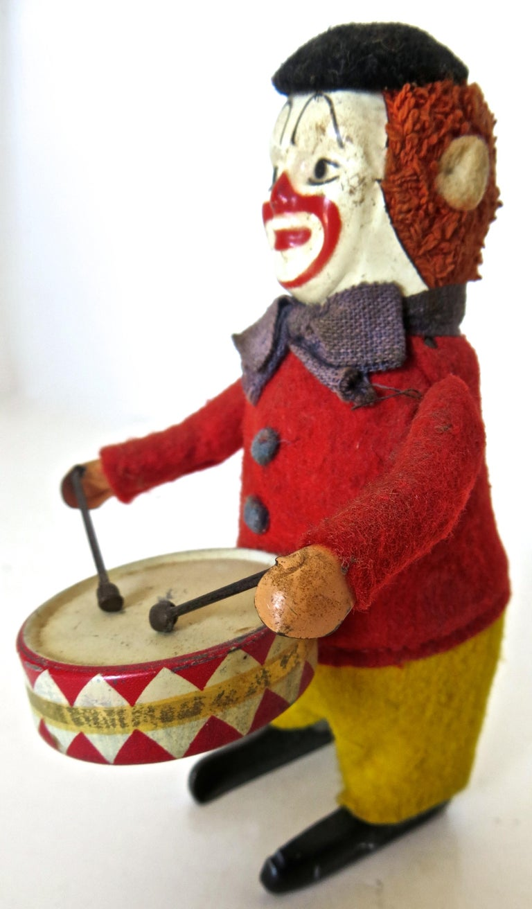 When wound up this charming German Schuco toy clown dances around, while raising his arms up and down playing the drum. In excellent all original condition, he has a tin face and drum, and in dressed in a red felt vest with yellow trousers, and a