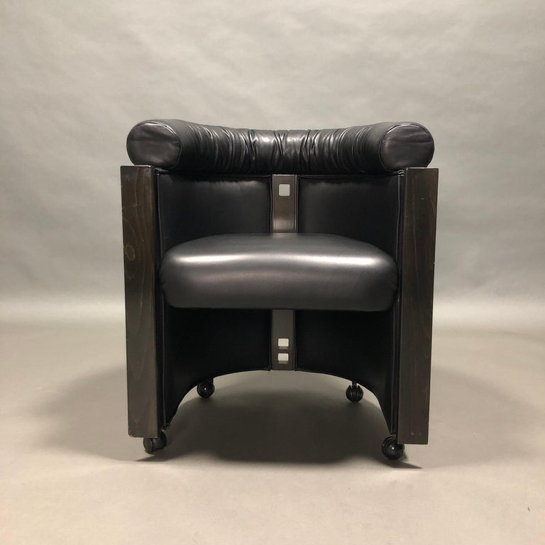 Elegant and very rare club chair by Umberto Asnago for Giorgetti, Italy, 1980s.  The chair is made of black leather and ebonized Oak. The back of the chair is also covered in leather. The base has four wheels.  Designer: Umberto