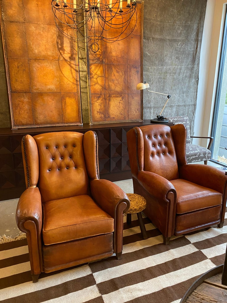 Pair of cognac leather wingback chairs with tufted backs and large nailheads. Nicely matched pair in good condition. Leather has luster, patina and shows some repair. Unusually comfortable and generous scale in comparison to many of the same period.