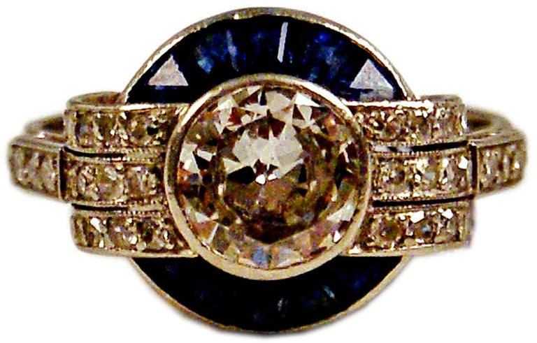 Art Deco Gorgeous Cluster Ring: PLATINUM  &  ONE LARGE DIAMOND IN MIDDLE AREA  (VINTAGE CUTS / 1.0 Carat) plus smaller diamonds and sapphires     Most elegant Art Deco Cluster Ring of French manufactory:  One large diamond (1.0 Carat) attached to