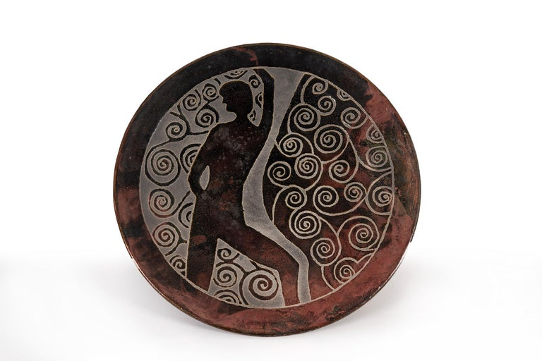 Clyde Burt ceramic charger in glazed stoneware with incised image.