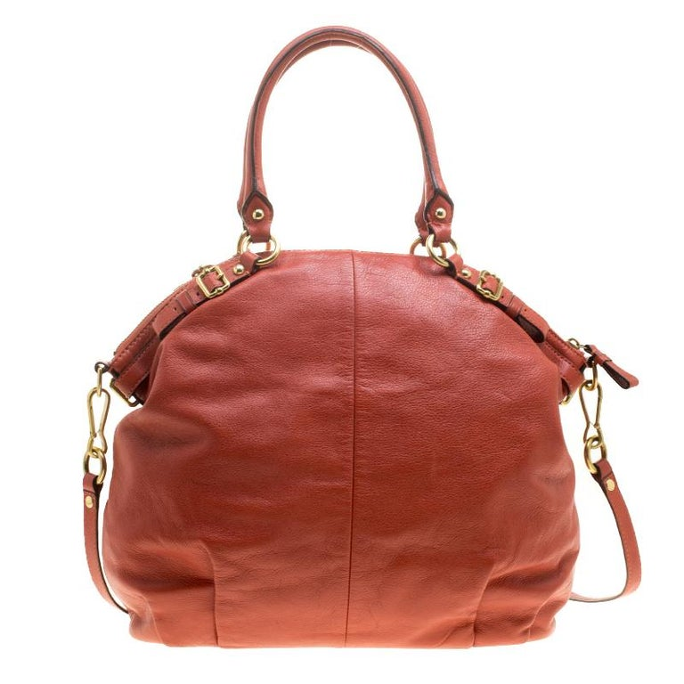 Meticulously crafted from orange leather, this Coach satchel exudes just the right amount of style and feminity. The bag features a spacious interior with satin lining and a zipped pocket. It is complete with dual top handles and a detachable